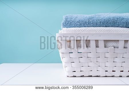 Laundry Concept. Stack Of Clean Towels In A White Laundry Basket Isolated On Blue Background