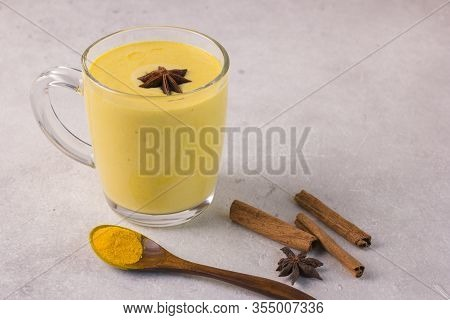 Golden Milk With Turmeric In A Glass Cup And Cinnamon Sticks On A Gray Background.