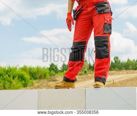 Low Section Legs Of Construction Worker Wearing Workwear Trousers And Brown Leather Work Boots Stand