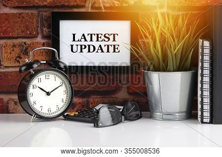 Latest Update Text With Alarm Clock, Books And Vase On Brick Background. Business, Quotes And Copy S