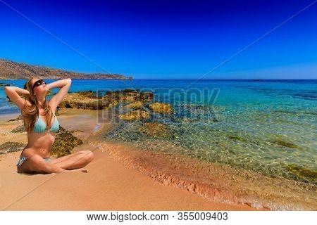 Beautiful blonde young woman in on tropical beach. Portrait of happy young woman in swimwear enjoying sun on beach.
