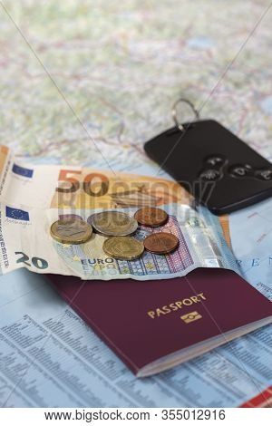 Euro Banknotes And Coins Lie On The Road Map. The Passport And Car Keys Also Lie On A Paper Map.