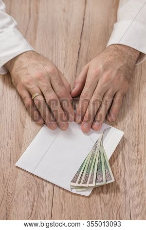 Man In A White Shirt Holds The Tip Of His Fingers With A White Envelope Filled With Polish Zloty Ban