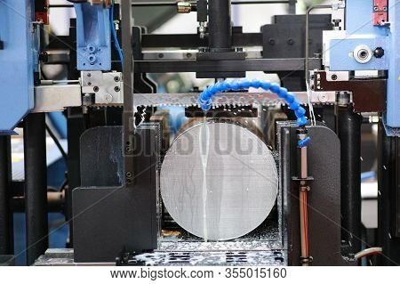 The Industrial Sawing Machine Cutting The Steel Rod With Coolant Fluid.the Band Saw Machine Cutting
