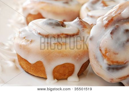 Delicious freshly baked cinnamon rolls on decorative plate.  Macro of 'mini' rolls with extremely shallow dof.