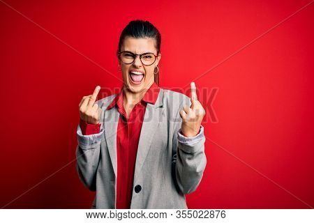 Young beautiful brunette businesswoman wearing jacket and glasses over red background Showing middle finger doing fuck you bad expression, provocation and rude attitude. Screaming excited