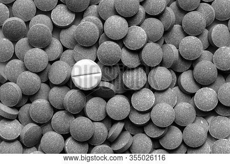 Pile Of Dark Pills Around A White One, Low Key Monochrome. Medication, Self-treatment Or Placebo Con