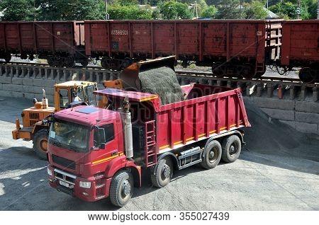 Wheel Loader Loads Gravel Into A Dump Truck At A Cargo Railway Station. Fron-end Loader Unloads Crus
