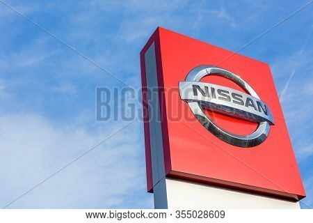 Nissan Brand Logo On Bright Blue Sky Background Located On Its Dealer Office Building In Lyon, Franc