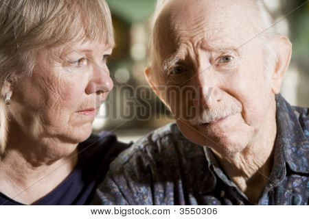Close Up Portrait of Worried Senior Couple poster