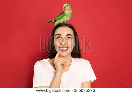 Young Woman With Alexandrine Parakeet On Red Background. Cute Pet