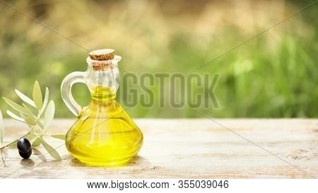 Glass Bottle Full Of Extra Virgin Olive Oil Made In Puglia, Salento On A Wooden Table With Olive Bra