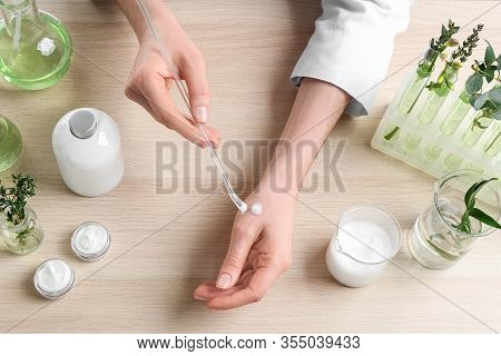Woman Applying Natural Cream Onto Hand In Cosmetic Laboratory, Above View