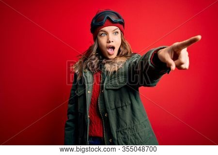 Young blonde girl wearing ski glasses and winter coat for ski weather over red background Pointing with finger surprised ahead, open mouth amazed expression, something on the front