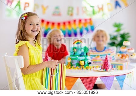 Child Birthday Party. Kids Blow Candle On Cake.