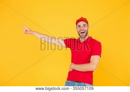 Delivery Concept. Portrait Of Smiling Deliveryman. Shows Away. Mail Service, Job And People Concept.