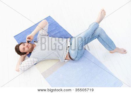 gutaussehend junger Mann am Boden zu Hause, Gespräch am Mobiltelefon, lächelnd.
