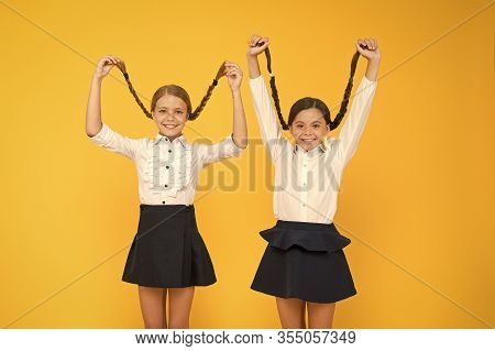 Long Hair Growth Stimulant. Cute Small Children Holding Long Hair Braids On Yellow Background. Adora
