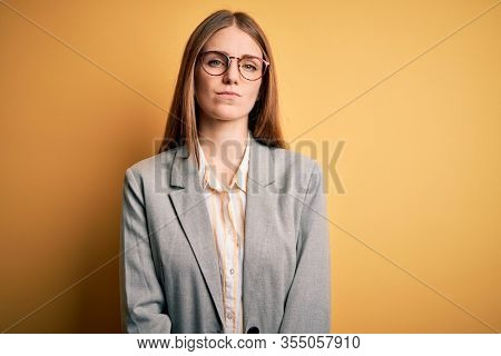 Young beautiful redhead woman wearing jacket and glasses over isolated yellow background Relaxed with serious expression on face. Simple and natural looking at the camera.