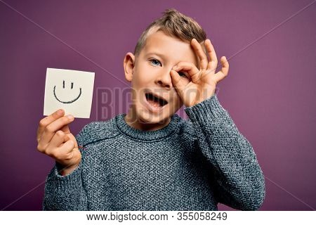 Young little caucasian kid showing smile face on a paper note as happy message with happy face smiling doing ok sign with hand on eye looking through fingers