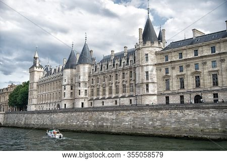 Palace On Stone Embankment. Boat Tour. Palais De La Cite In Paris France. Palace Building With Tower