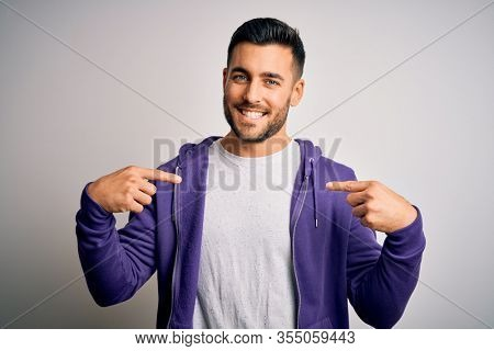 Young handsome man wearing purple sweatshirt standing over isolated white background looking confident with smile on face, pointing oneself with fingers proud and happy.