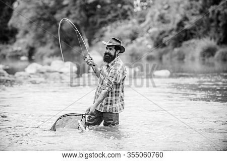 Bearded Fisher In Water. Young Man Fishing. Successful Fly Fishing. Fisher Masculine Hobby. Man With
