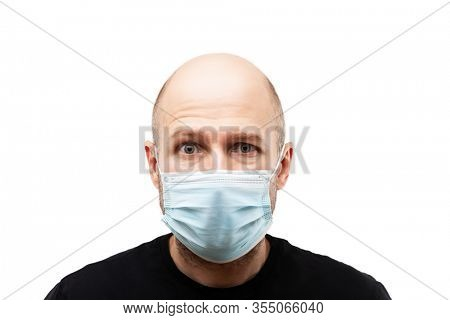 Human population virus, infection, flu disease prevention and industrial exhaust emissions protection concept - young adult bald head man wearing respiratory protective medical mask white isolated
