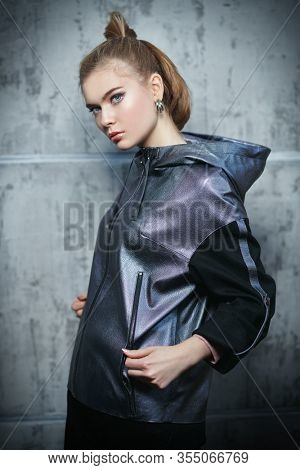 Fashion shot. Attractive young woman in trendy silver gray jacket posing on a grunge background.