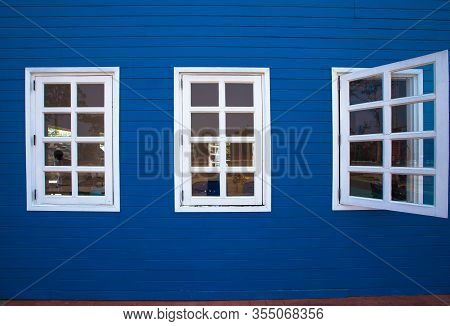 Wooden Rustic Window In Small Cottage House. Vintage Blue Paint Wall With Transparent Glass Window A