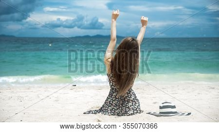 Summer Time Tan Woman Vacation On The Beach. Cheerful Woman Wear Summer Dress And Straw Hats Sitting