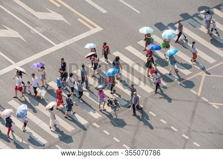 Chengdu, Sichuan Province, China - June 12, 2019 : People With Umbrellas Walking On A Zebra Crossing