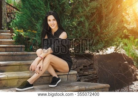 Pretty Brunette Thoughtful Girl Sitting On Stone Stairs Among The Pine Trees In The Summer Park