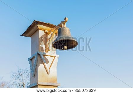 Copper Bell On A Wooden Post, Signal Bell. Antique Devices For Warning Of Misfortune, Gathering Peop