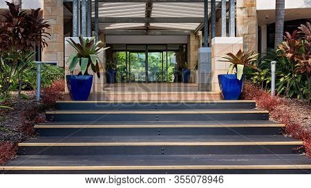 Entry Up Stairs With Pot Plants On Either Side, Across A Patio And Into Glass Doors