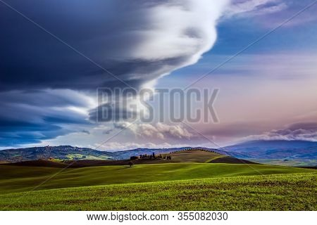 Agritourism. Rural farms and  picturesque hills of Tuscany after harvest. Gorgeous powerful clouds over Tuscany hills. Beautiful Italy. The concept of active, rural and photo tourism