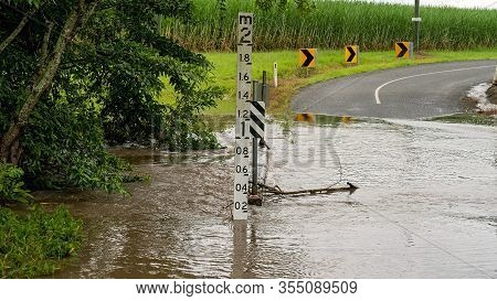 Water Over The Road From An Overflowing Creek Caused By Heavy Tropical Rainfall. Sign Indicates Dept