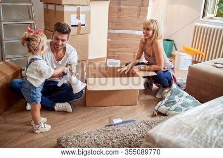 little girl playing with her dad and mom in new apartment. new apartment, new beginning, joy, playful, carefree  concept
