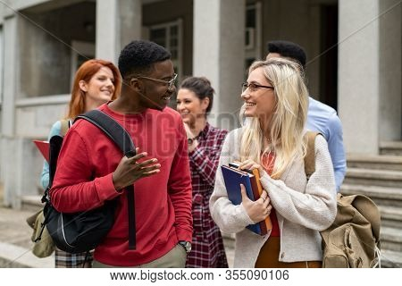 Group of happy multiethnic students walking outside college building. Five university students holding books and school backpack while talking together. Young man and beautiful girl in conversation.