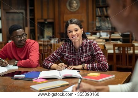 Happy multiethnic students preparing for exams together. Smiling young girl in high school making notes while looking her friend. Group of university students studying in library while researching.