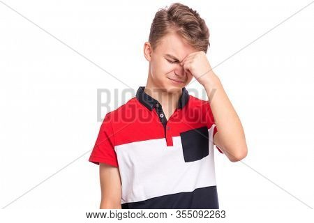 Portrait of tired teen boy touching his head suffering headache. Unhappy beautiful caucasian young teenager suffering from headache. Sad teenager isolated on white background.