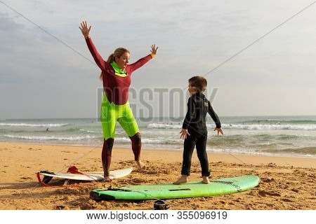 Mother And Son Standing On Surfboards. Cheerful Middle Aged Woman Showing Little Son How Standing On