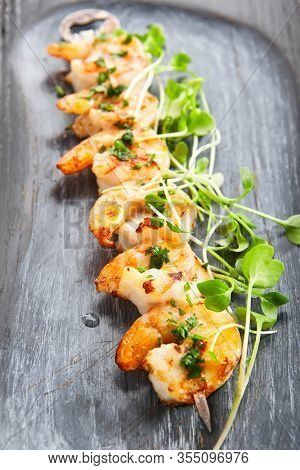 Shrimp kebab close up view. Tasty seafood with greenery. Roasted prawns with garden cress on wooden tray.  Culinary presentation, food composition. Delicious restaurant meal, haute cuisine