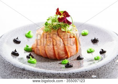 Salmon olivier salad with sauces. Sliced fish dish with greenery. Tasty seafood decorated with violet flower. Haute cuisine on plate closeup view. Restaurant meal, elegant food composition