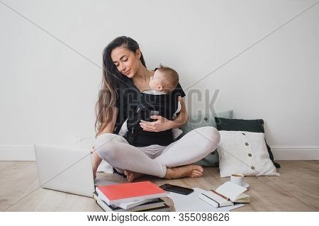 Young Freelance Mother Having Her Baby In Ergo Backpack And Working At Home Using Laptop And Smart P