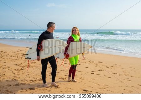 Happy Couple With Surfboards Walking On Beach. Cheerful Man And Woman In Wetsuits Holding Surfboards
