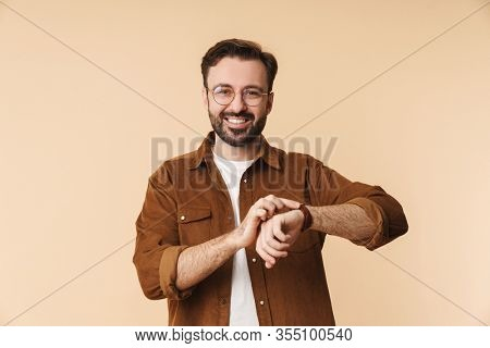 Portrait of a cheerful young arttractive bearded man wearing casual clothes standing isolated over beige background, checking time
