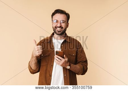 Portrait of a cheerful young arttractive bearded man wearing casual clothes standing isolated over beige background, using mobile phone, thumbs up
