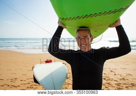 Father And Son Holding Surfboards. Happy Father And Cute Little Son In Wetsuits Holding Surfboards O