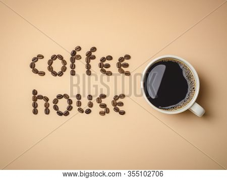 Top View Of Roasted Coffee Beans Arranged In Letters And Hot Coffee In White Coffee Cup On Light Bro